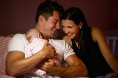 Parents At Home Cuddling Baby Daughter In Nursery Stock Image