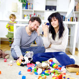 Parents at home desperate about mess of toys. Cute little girl making mess with toys while parents are very tired Stock Image