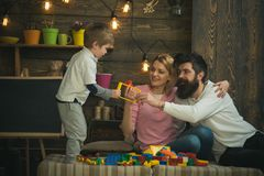 Parents hug each other while playing with kid. Side view standing blond boy taking plastic constructor details from dad. Happy family concept stock photography