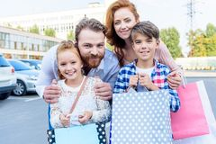 Parents hugging children with shopping bags standing on street. After shopping royalty free stock photos