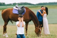 parents hugging and son covering eyes on foreground royalty free stock photos