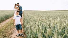 parents hugging and son looking at camera on path stock photo