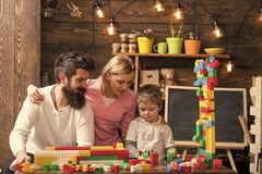 Parents hugs, watching son playing, enjoy parenthood. Family leisure concept. Kid with parents play with plastic blocks. Build construction. Father, mother and stock image