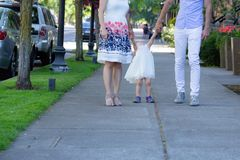 Parents, husband and wife, walk with their girl toddler royalty free stock image
