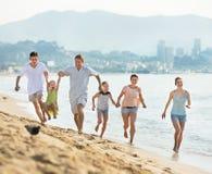 Parents i bambini che corrono sulla spiaggia Immagini Stock