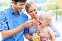 Parents il bambino d'alimentazione dal cucchiaio Immagini Stock Libere da Diritti