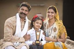 Parents indiens ruraux avec le trophée de participation de fille images stock