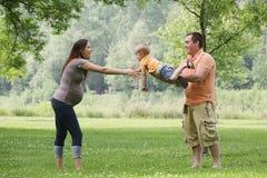 Parents jouant avec le fils à l'extérieur. photos libres de droits