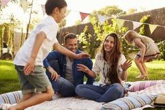 Parents jouant le jeu avec des enfants sur la couverture dans le jardin images libres de droits