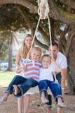 Parents joyeux poussant leurs enfants sur une oscillation Images libres de droits