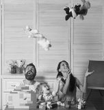 Parents and kid with happy faces tossing and catching plush toys. Family time concept. Family playing with plastic royalty free stock images