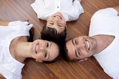 Parents and kid lying on floor with heads together Stock Photo