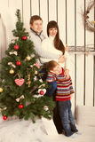 Parents and kid near Christmas tree. Stock Photo