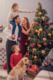Parents and kids beautifying Christmas tree. Friendly family is preparing for New Year together. They are decorating fir-tree and smiling. Girl is sitting on Stock Image