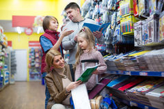 Parents and kids buying writing materials Stock Image