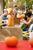 Parents And Kids Carve Pumpkins In A Public Park Stock Photo