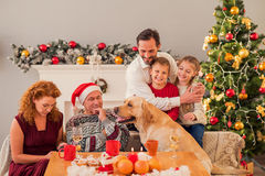 Parents and kids celebrating Christmas with pet. Friendly family is sitting at the holiday table and smiling. Mother is embracing children with love. Dog is Royalty Free Stock Photos