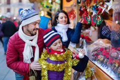 Parents with kids choosing X-mas decorations in market. Ordinary happy  positive parents with kids choosing X-mas decorations in market Royalty Free Stock Images