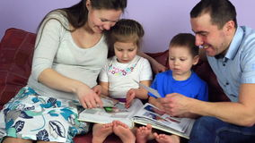 Parents with kids consider an album with photos. Happy family waiting for third child. stock footage