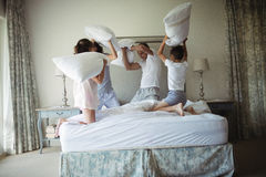 Parents and kids having pillow fight on bed. In bedroom stock photos