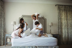 Parents and kids having pillow fight on bed. In bedroom stock photography