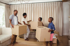 Parents and kids holding cardboard boxes in living room Royalty Free Stock Images