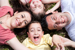 Parents and kids laying on the floor. With heads together, outdoors Royalty Free Stock Photo