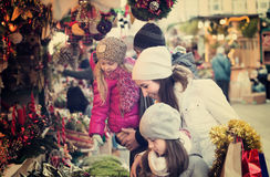 Parents with kids at X-mas market. Young parents with two little daughters choosing X-mas decorations in market. Focus on woman Royalty Free Stock Photography
