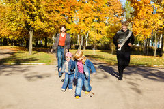 Parents and kids in park. Parents running down their kids in the autumn park Stock Photo