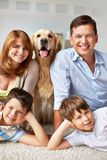 Parents, kids and pet. Happy young couple, their sons and fluffy pet Stock Image