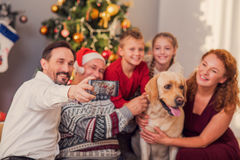 Parents and kids photographing with pet on holiday. Friendly family is making selfie on smartphone and smiling. They are sitting near Christmas tree and stock image