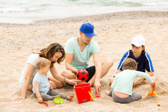Parents and kids playing with sand. At sea shore Royalty Free Stock Image