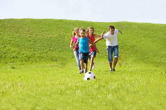 Parents and kids running. To the ball Royalty Free Stock Image