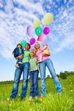 Parents and kids stand with balloons in park Royalty Free Stock Images
