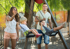 Parents with kids at swings Royalty Free Stock Photos