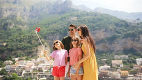 Parents and kids taking selfie photo background Positano town in Itali on Amalfi coast stock video
