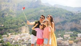 Parents and kids taking selfie photo background Positano town in Itali on Amalfi coast stock footage