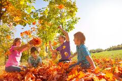 Parents and kids throw leaves in the air together. Parents and kids throwing leaves in the air during play while sitting on grass during beautiful sunny autumn Royalty Free Stock Photo