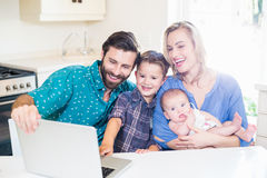 Parents and kids using laptop in living room. At home Stock Photos