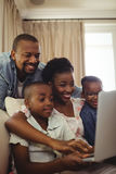 Parents and kids using laptop in living room. At home Royalty Free Stock Images