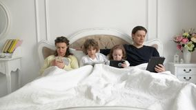 Parents and Kids Using Mobile Devices Together in the Bedroom During Weekend at Home. Young Couple with Children are. Lying on the Bed Holding in Hands stock footage