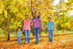 Parents and kids walking together holding hands. In a row in the park during beautiful sunny autumn day Royalty Free Stock Photos