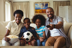 Parents and kids watching television in living room Stock Photography