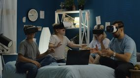 Family in VR glasses sitting on bed. Parents and kids wearing goggles and watching VR 360 game while sitting on bed all together enjoying new feelings stock footage