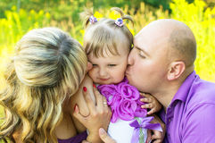 Parents kiss the child on the cheek Royalty Free Stock Photography