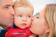 Parents kiss child outdoors Stock Photography