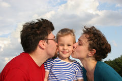 Parents kiss son. And sky Stock Image