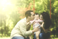 Parents kiss their child on swing. Two young parents kissing their daughter on a swing at the park Royalty Free Stock Photos