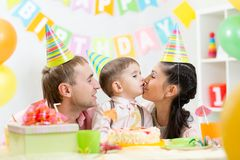 Parents kiss their son celebrating child birthday Stock Photos