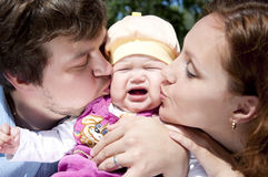 Parents kissing baby. Father and mother kissing a child, the child is crying and sad Stock Image